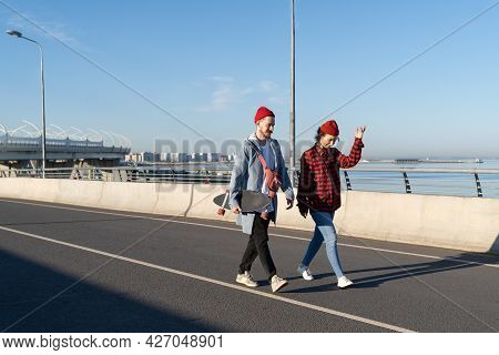 Young Man And Woman Walking On Bridge Together Talking, Stylish Hipsters On Date. Millennial Casual