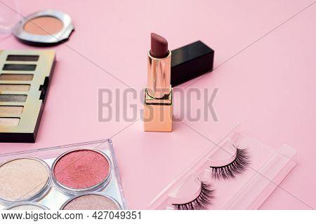 Decorative Cosmetics On A Pink Background. Focus On Lipstick. False Eyelashes, Eye Shadow, Blush And