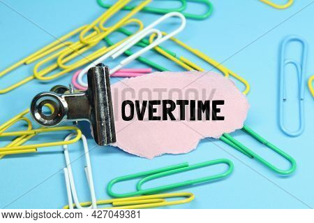Paper Clips, Clamps, Red Torn Paper With The Word Overtime