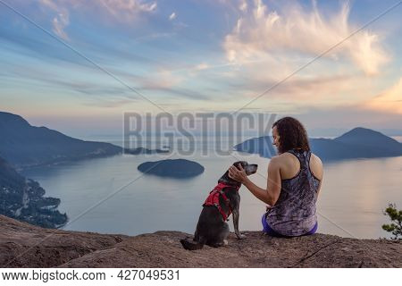 Adventurous Caucasian Adult Woman Hiking On Top Of A Mountain With A Dog. Colorful Sunset Sky. Tunne