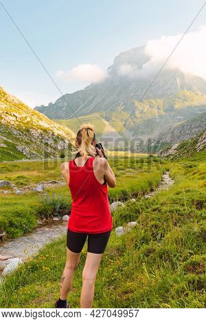Caucasian Young Woman From Behind Next To A River And Near A Mountain Taking Pictures Of The Landsca
