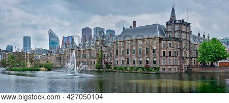 Panorama of the Binnenhof House of Parliament and the Hofvijver lake with downtown skyscrapers in background. The Hague, Netherlands