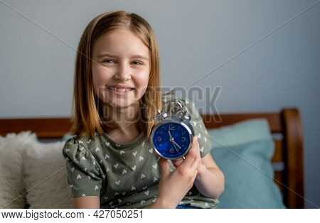 Portrait of preteen beautiful blond hair girl with blue clock in bedroom. Female kid schoolgirl sitting in the bed and looking at the camera smiling