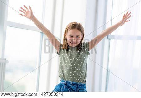 Portrait of preteen beautiful girl posing in light room with hands up and smiling. Female kid schoolgirl looking at the camera indoors