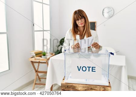 Hispanic business woman voting putting envelop in ballot box looking sleepy and tired, exhausted for fatigue and hangover, lazy eyes in the morning.