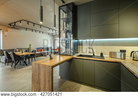 Modern luxury loft studio apartment interior with dining table in large living room, kitchen counter at first plane