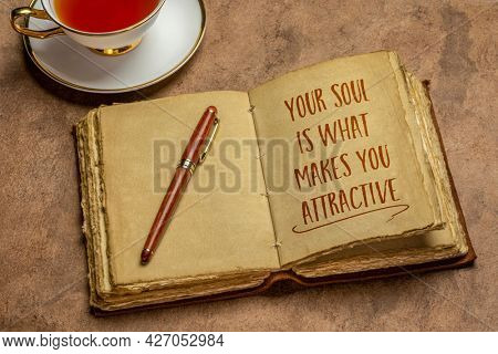 your soul is what makes you attractive - inspirational handwriting in leather-bound journal with a stylish pen and cup of tea against handmade paper, spirituality and personal development concept