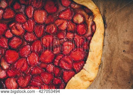 Close Up Of Fresh Baked Strawberry Galette On Baking Paper. View From Above