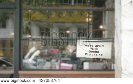 Defocused Restaurant With Notice On Windows, We're Open With Social Distancing. New Normal During Co