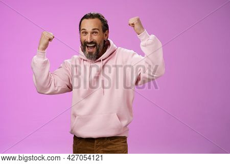 Yeah Who Cares Age. Carefree Delighted Happy Old Man Bearded In Trendy Pink Hoodie Raise Fists Joyfu