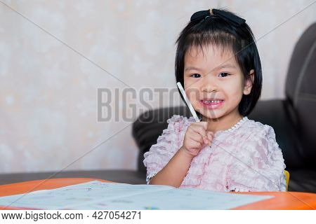 The Little Girl Smiled Sweetly, Looked At The Camera And Held A Pencil On His Cheek. Happy Learning