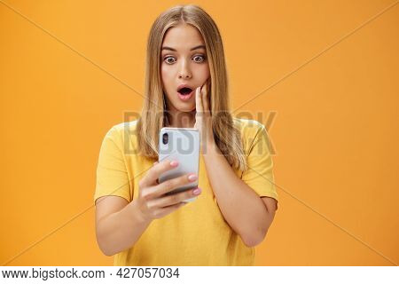 Waist-up Shot Of Shocked And Stunned Emotive Young Woman Reacting To Shocking Terrible News Reading