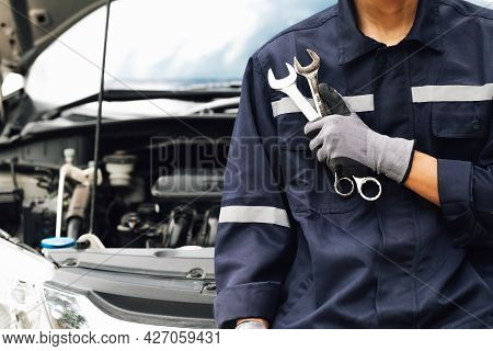 Hand Of Car Mechanic With Wrench. Auto Repair Garage. Mechanic Works On The Engine Of The Car In The