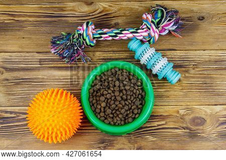 Dog Toys And Feed For Dogs In Green Plastic Bowl On Wooden Background. Top View. Dog Care Concept