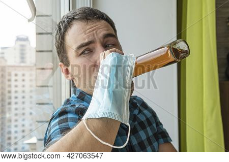 Alcoholism, Alcohol Addiction And People Concept - Male Alcoholic With Bottle Of Rum At Home. An Une