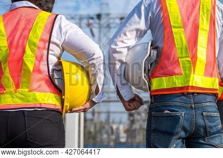 View From Behind, Two Electricians Holding Yellow And White Safety Helmets Wearing Reflective Clothi