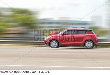 Samut Sakhon, Thailand - April 2021: Suzuki Swift, Red Car Driving With Speed-effect With Blur Backg
