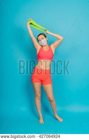 Woman In Face Protection Mask And Fitness Wear Isolated Over Blue Background.