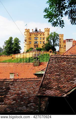 Schloss Hohenschwangau Castle Against The Sky With Clouds. Rustic Tiled Roofs. Upper Swan County Pal