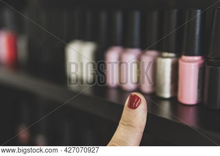 The Choice Of Nail Polish. A Finger With A Red-painted Fingernail Points At The Bottles Of Nail Poli