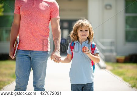 School Boy Going To School With Father. Kid Elementary Student Carrying Backpacks Holding Parent Fat