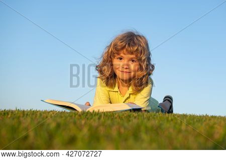 Boy Child Reading Book, Lying Down On Green Grass.