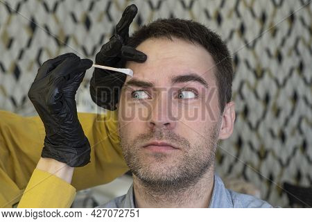 Beautician Plucking Beautiful Bearded Man Eyebrows With Tweezers In Beauty Salon. Female Hands Pluck