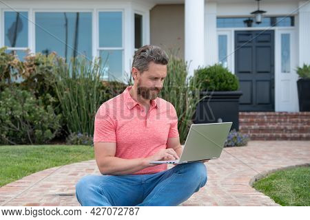 Portrait Of Young Successful Real-estate Agent Standing Outdoor At Dwelling For Sale. Selling Houses