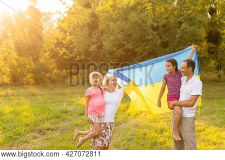 Flag Ukraine In Hands Of Little Girl In Field. Child Carries Fluttering Blue And Yellow Flag Of Ukra