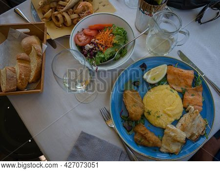 Image Of Assorted Fried Fish With Polenta Mixed Salad And Bread On A Blue Plate