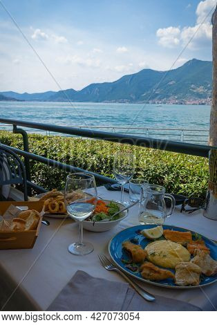 Assorted Fried Fish With Polenta And Salad On Blue Plate On Table Against Background Of Lake Iseo In