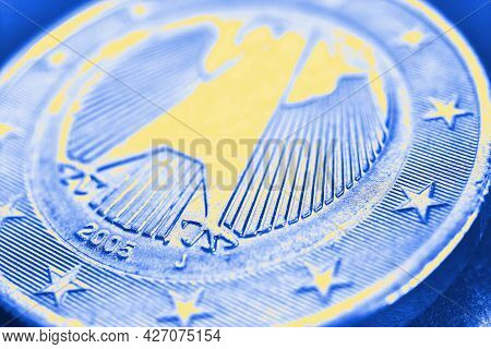 1 Euro Coin Issued In Germany Close-up. Obverse With The Federal Eagle. Blue And Yellow Tinted Econo