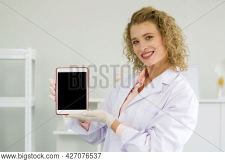 Young Blonde Scientist Holding Blank Screen Tablet Computer. Working Atmosphere In Chemical Laborato