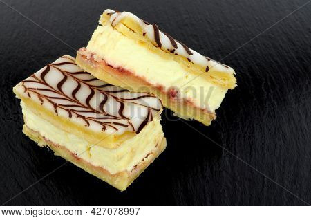 Fresh Dairy Cream Filled Vanilla Slices Made With Puff Pastry Topped With Icing And Chocolate Flavou