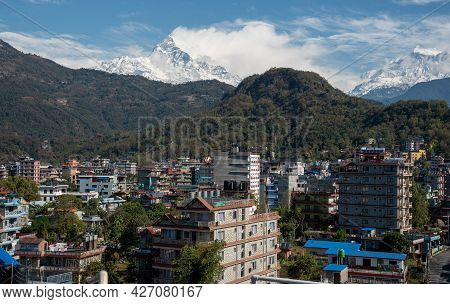 Pokhara, Nepal, March 15 2020: The Cityscape Of Pokhara With The Annapurna Mountain Range Covered In