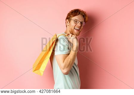 Carefree Young Man With Red Hair And Glasses, Walking With Shopping Bag Over His Shoulder And Smilin
