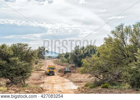 Vondeling, South Africa - April 21, 2021: A Frontloader, Clearing Sand From A Causeway In The Traka