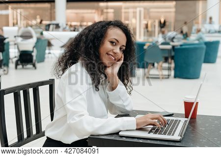 Young Woman Works On A Laptop In A Cafe Shopping Mall.
