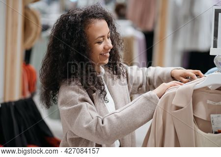Young Woman Choosing Clothes In The Store.