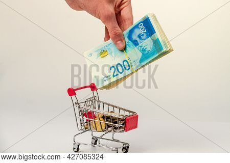 A Man's Hand Places A Stack Of 200 Israeli Shekels Into A Grocery Cart Containing Israeli Coins.