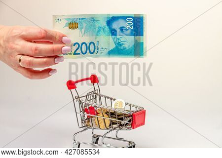 A Woman's Hand Holds A 200 Israeli Shekel Bill Over A Grocery Cart Filled With Israeli Coins On A Li