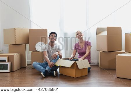 Happy Caucasian Couple Sit On With Stuff In Boxes Moving To New Home. Adult Men And Women Look At Th