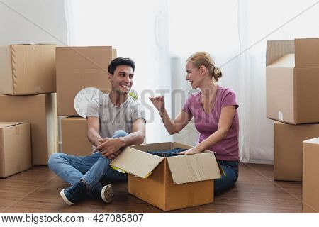 Happy Caucasian Couple Sit On With Stuff In Boxes Moving To New Home. Adult Men And Women Consult An