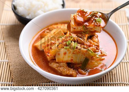 Korean Food, Kimchi Soup With Tofu And Pork In A Bowl Eating By Spoon