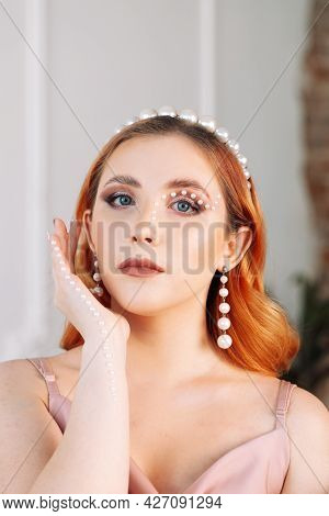 Close-up Portrait Of A Lop-eared Woman In A Silk Dress With Makeup Made Of Mother-of-pearl Pearls, W