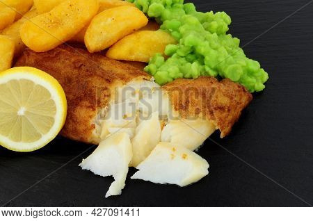 Battered Cod Fish Fillet With Chunky Chips And Mushy Peas On A Slate Stone Background