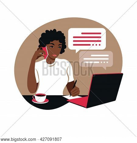 African Woman Works On A Laptop Computer And Talks On The Phone Sitting At A Table At Home With A Cu