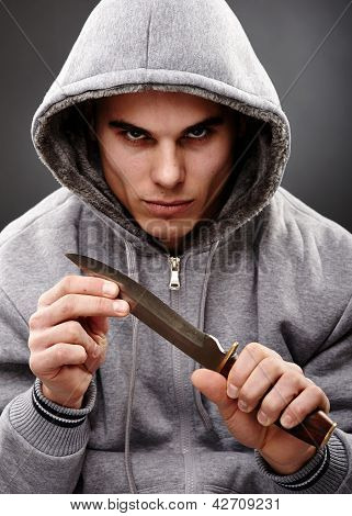 Closeup portrait of a threatening mafia man holding a knife in his hands over gray background representing the concept of danger poster