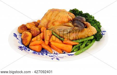 Roasted Whole Guinea Fowl With Roast Potatoes And Fresh Vegetables Isolated On A White Background