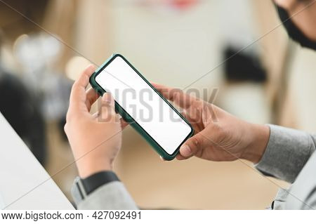 Cropped Shot Of A Man Hands Holding Smart Phone Device With Blurred Office Background.